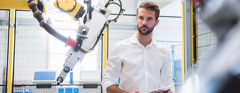 Mann prüft Arbeitsroboter